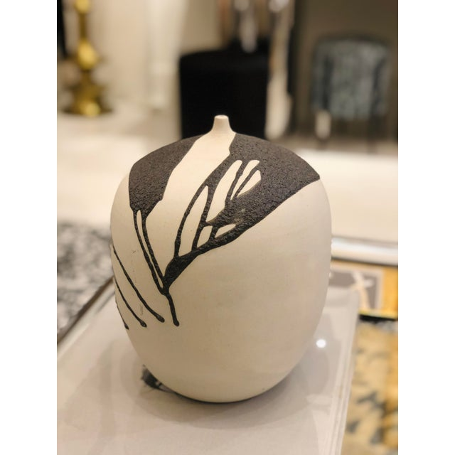 This is a beautiful ceramic vase made by a studio ceramicist. It has a unique look; the ceramic is a off-white tone, sort...