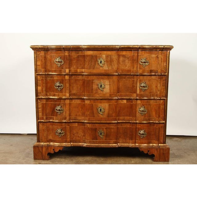 A Danish Rococo chest of drawers, consisting of four drawers, with gilt bronze hardware and gilt borders. This Danish...