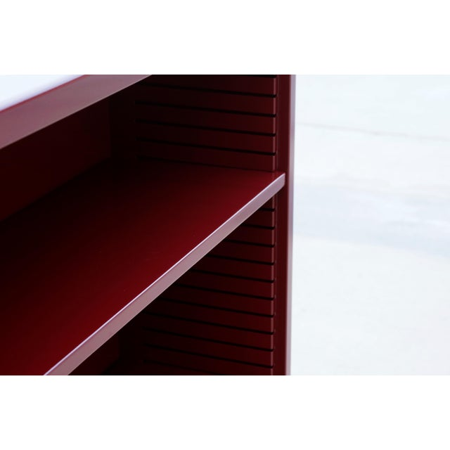 Neat 1960s tanker style steel bookcase freshly powder coated in high gloss wine red. Originally used in the UCLA math...