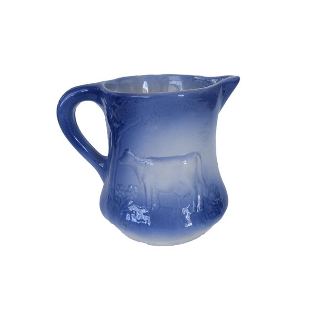 """Antique blue and white ironstone pitcher. Cow motif on both sides. Marked Ironstone England 1890. Measures 6.5"""" h x 5""""..."""