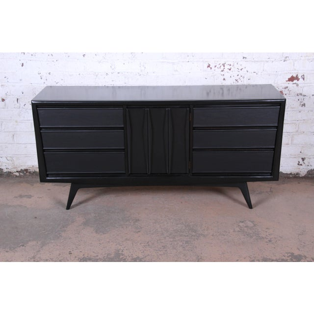 A gorgeous mid-century modern sculpted walnut triple dresser or credenza by United Furniture. The dresser features...