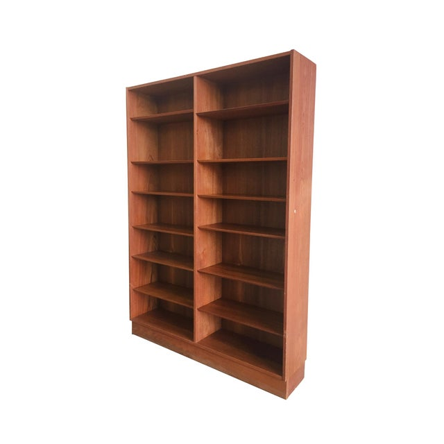 A modern bookcase streamlined into a minimal, elegant form. Designed by Poul Hundevad. Mid-20th Century. The bookcase is...