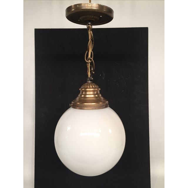 Offered is a vintage brass-colored ceiling pendant lamp, with a white frosted glass globe. In excellent condition. Ceiling...