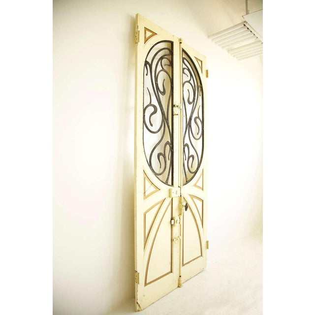 Art Nouveau doors featuring sculpted Metal with gold painted details and brass doorknob.
