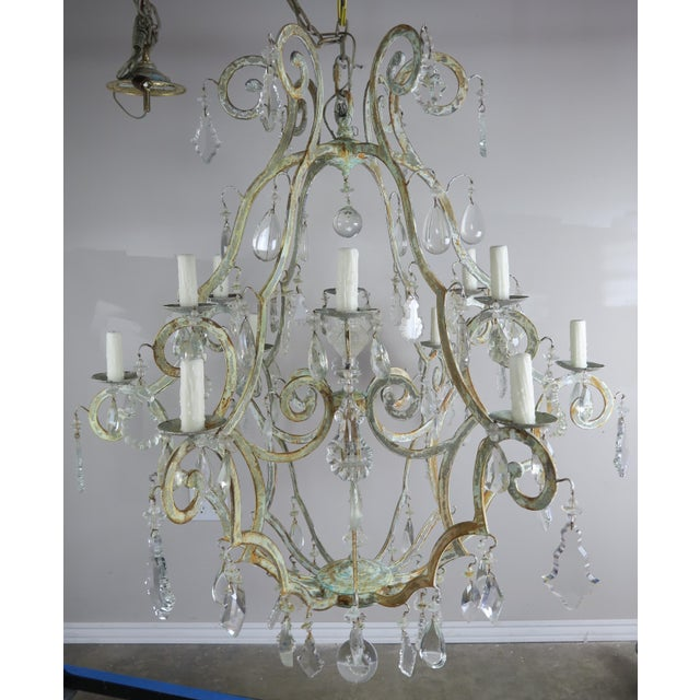Italian wrought iron twelve-light chandelier with a beautiful soft painted finish depicting shades of worn paint from...