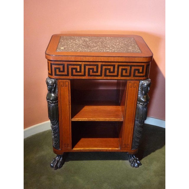 A Regency Period center table bookcase, executed in partridge wood, with an inlaid Ebony Greek key frieze containing one...