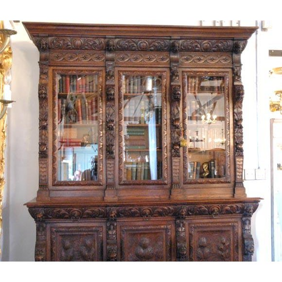 This bookcase has three glazed upper doors over three drawers and then three carved panel lower doors. The lower doors are...