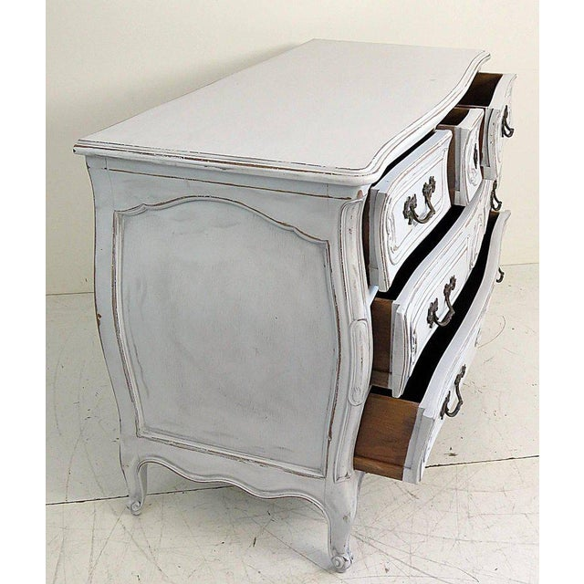 Pair of Swedish style Bombay commodes. Distressed antique white paint with 5 drawers and brass hardware.