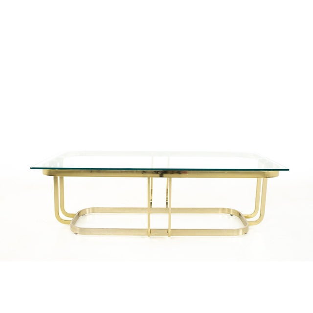 Milo Baughman Style Mid Century Brass and Glass Coffee Table Table measures: 53.75 wide x 24 deep x 19.75 inches high When...