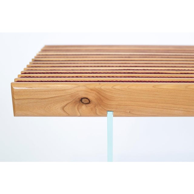 A series of rounded-edged, American cherry boards make up the bench surface, appearing reeded on the top face. Burgundy,...