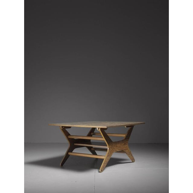 A rare Klaus Grabe table, made of an X-shaped pitch pine plywood base and a square top. By placing the base in a...