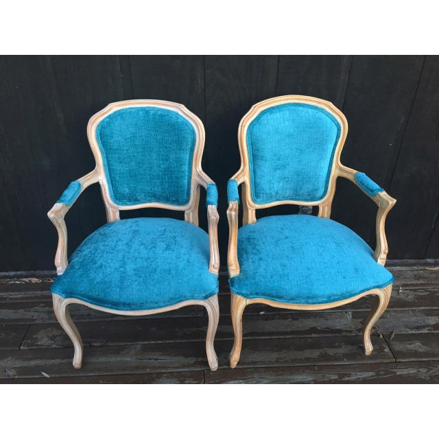 This dramatic pair of side chairs have bleached wood frames that have been treated with a worn, uneven, whitewash finish....