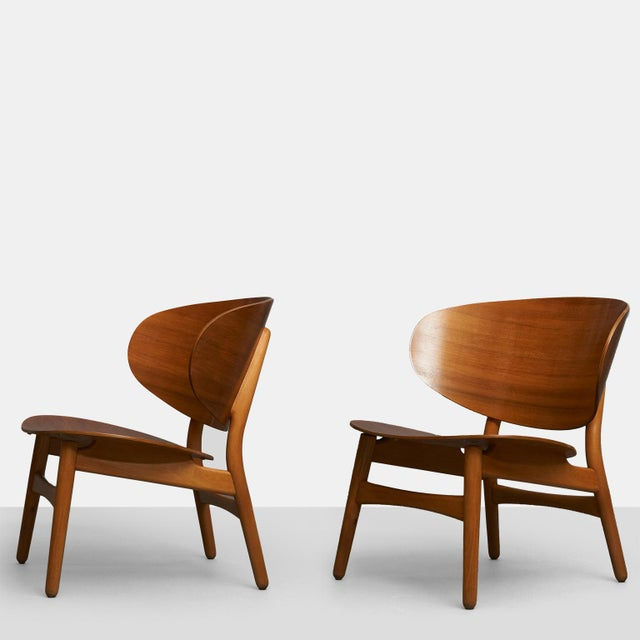 A pair of shell lounge chair by Hans Wegner. Features an oversized, laminated teak back and a maple frame with tapered...