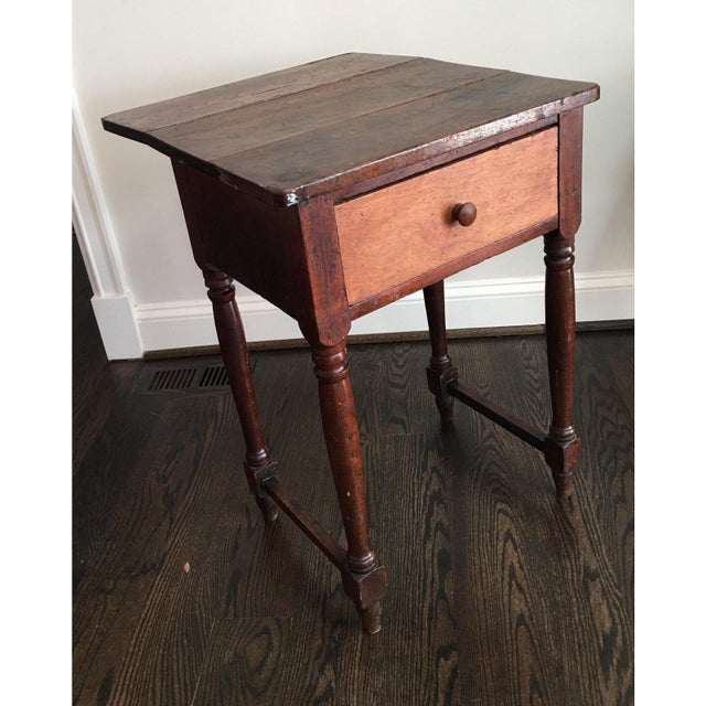 Charming rustic antique drop leaf work table with one drawer on baluster turned legs joined by stretcher. The table has a...