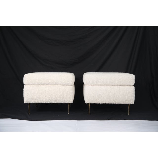 A gorgeous pair of Italian Mid-Century Modern white bouclé ottomans on brass legs. This magnificent pair of poufs are...