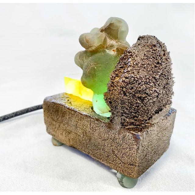 Bronze-cast sea sponge, epidote, golden calcite, LED lights, cloth-covered cord, 2019, 4.25 2.5 x 5 in. In Les Chants de...