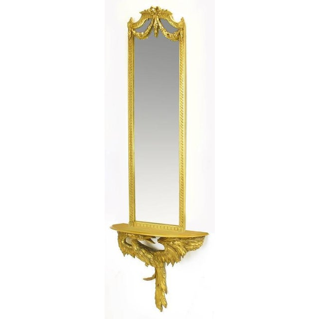 Italian hand carved and gilt fruit wood console mirror in the shape of a phoenix. Very intricate work with each feather...