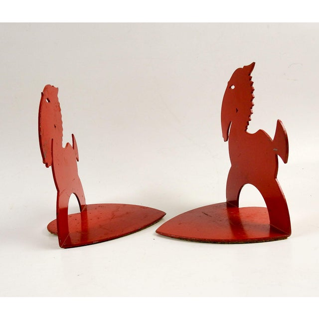 Graphic art deco metal horse bookends, painted red. Scratching to paint, felt bottoms.