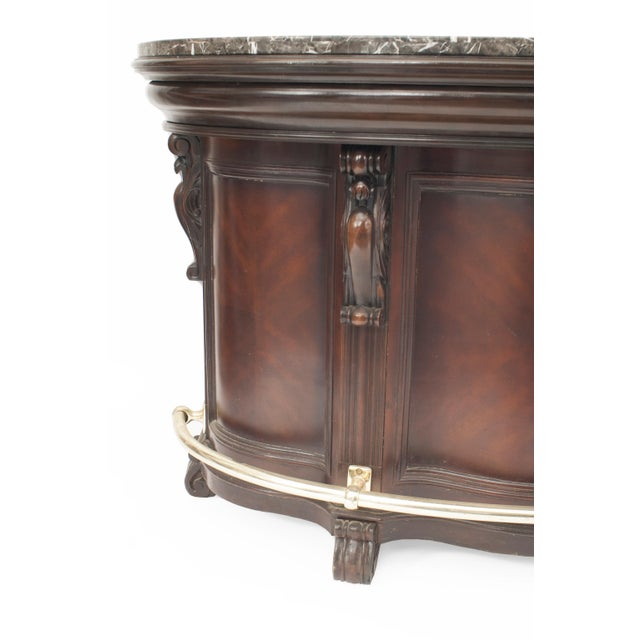 American Victorian style demilune shaped dark wood stained bar with a gray and black marble top with a brass foot rail and...