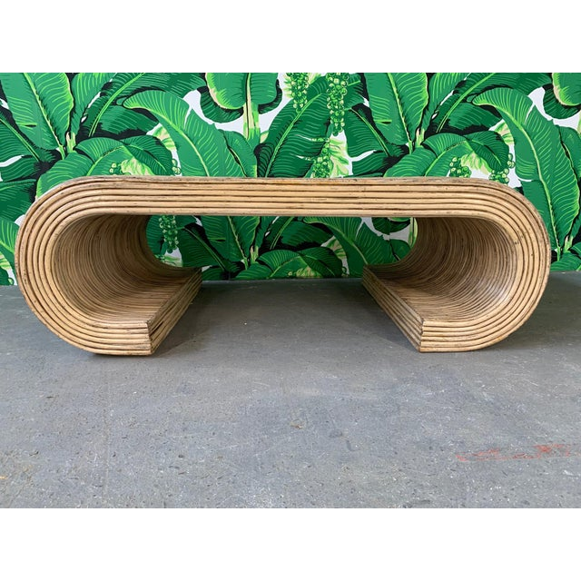 Scroll shaped coffee table features full rattan wrapping and sculptural form. Split reed wrap in the style of Gabriella...