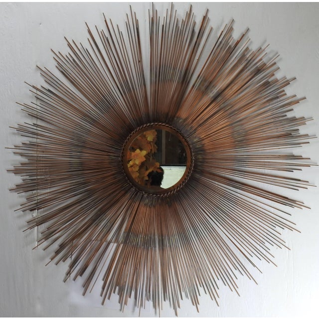 The sunburst on this stunning mirror showcases shades of copper on the metal. The mirror is framed with a twisted metal...