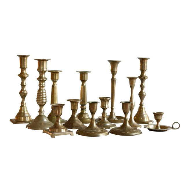 A set of 13 mismatched vintage brass candle holders. All are turned with open tops, bases are a variety of round, square...