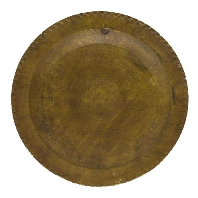 Fabulous wall decor! This large circular hammered brass tray, Mexico, 20th c. features a raised Toltec style figure in the...