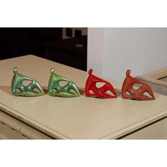 Two green and two red reclining Zsolnay ceramic figures, far right is SOLD, all with eosin glaze.