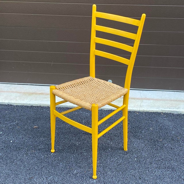 A slender yet sturdy ladderback side chair in a mustard yellow enamel finish with woven rope seat.