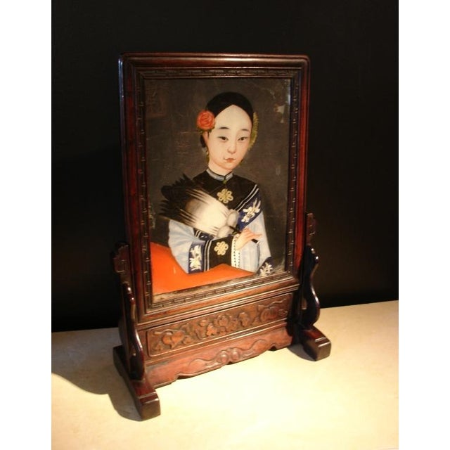 An unusual table screen featuring a reverse glass painted portrait of a young noble lady set into a hardwood frame and...