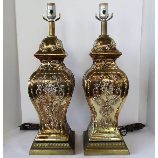 A pair of vintage Hollywood Regency style ceramic ginger jar lamps in gold glaze with an embossed floral design, dry-...