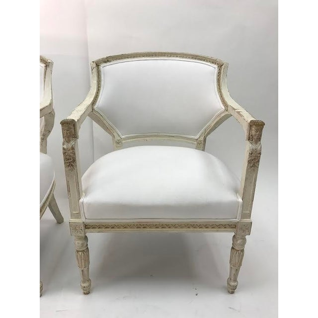 Stunning pair of antique white-painted Gustavian armchairs. Carved rosettes and rounded, fluted legs. These chairs are in...