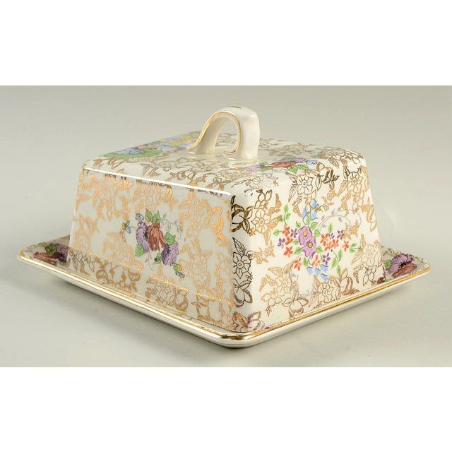 Lord Nelson Pompadour Cheese Dish With Lid features a multicolor lady in garden vignette and gold flower accents. This...