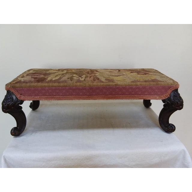 Tapestry covered footstool with carved mahogany legs.