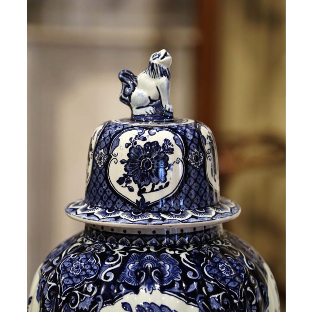 Crafted in Holland, circa 1940, the large faience potiche features hand painted medallions with Classic Dutch flower and...