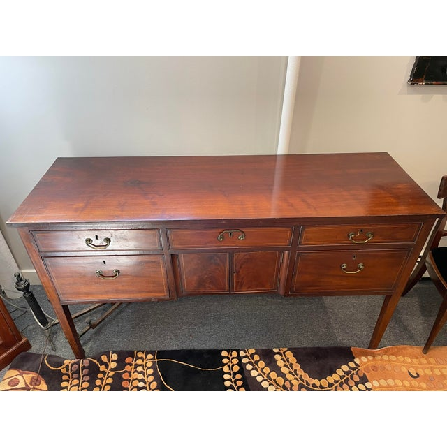 This is a gorgeous cherry wood sideboard. It is definitely vintage and has original brass hardware on it. It has straight...