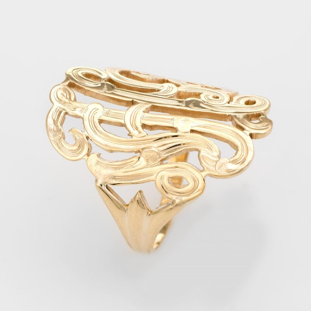 Finely detailed wide band ring (circa 1960s to 1970s), crafted in 14 karat yellow gold. The wide (1 inch) mount features a...