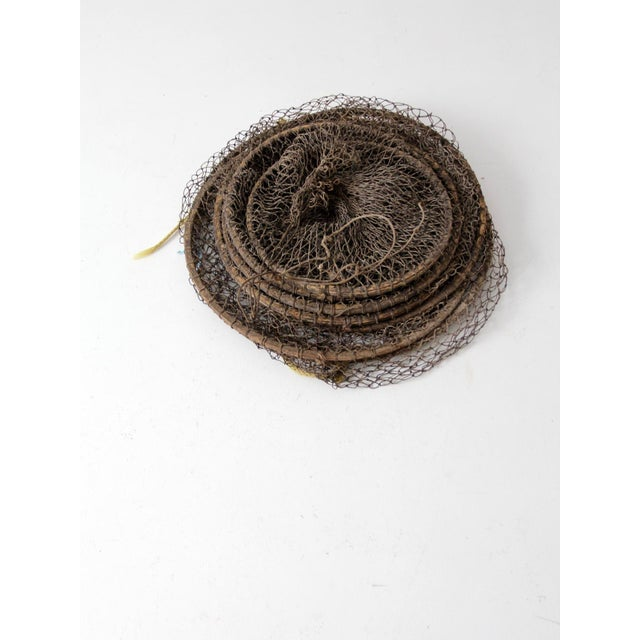 This is a vintage fyke net. The large fishing net features linked bag style nets held open by wooden hoops. A lovely...
