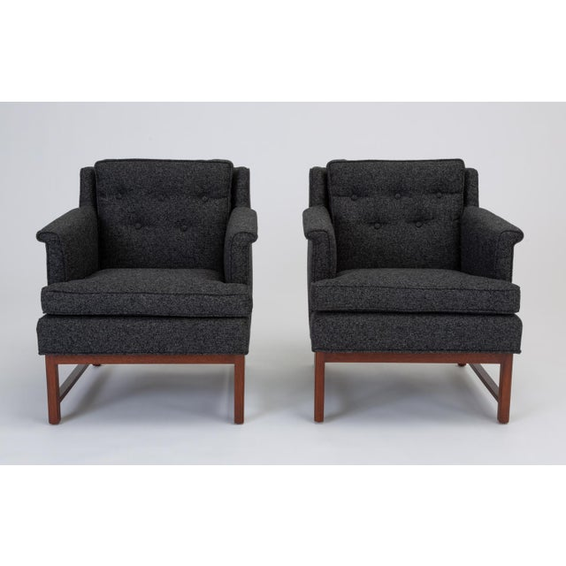 A pair of lounge chairs, upholstered in a heather midnight blue fabric, designed by Edward Wormley for Dunbar. The fully...
