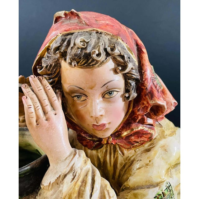 A 1970's vintage Italian porcelain sculpture or statue of a framer girl holding a jar. The statue features intricate...