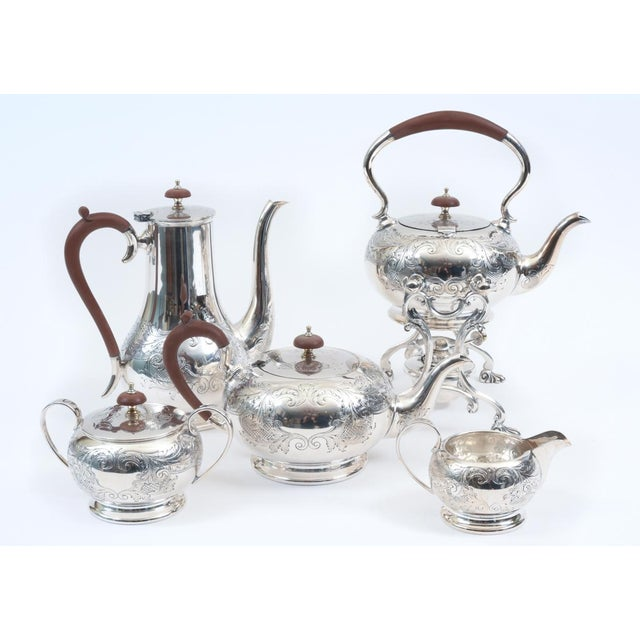 English silver plate with wood handle five-piece tea or coffee service with Kettle on stand. The tea or coffee service is...