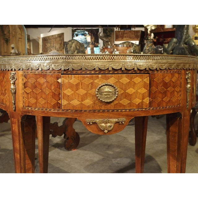 From France, this marble topped veneered parquet Bouillotte table dates to the 19th Century. The wooden veneer is a...