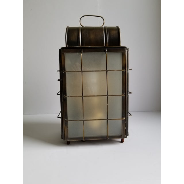 Vintage American Colonial style 1 light hanging wall lantern in an antique brass finish.The wall mounted lantern is wired...