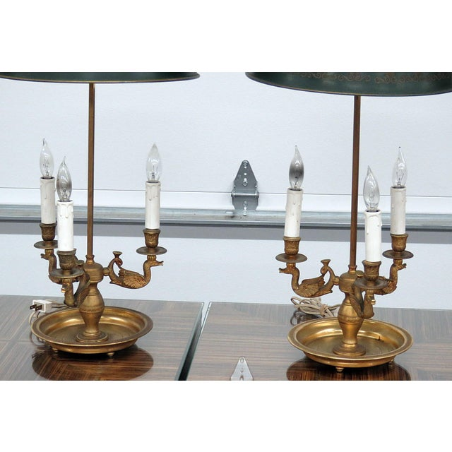 Pair of Empire style brass 3 arm bouillotte lamps with tole shades. Circa Early 20th Century.