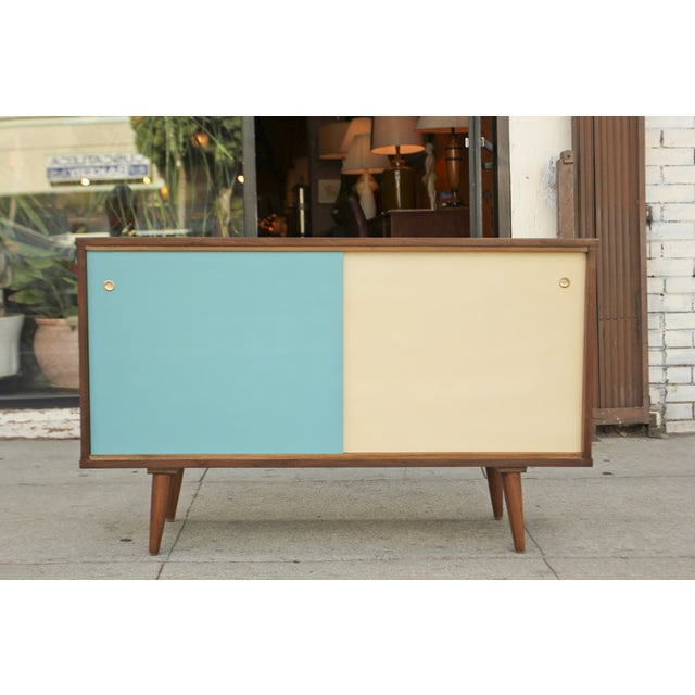 Super cool sliding door walnut credenza. There are two shelves both of which are adjustable for all your needs.
