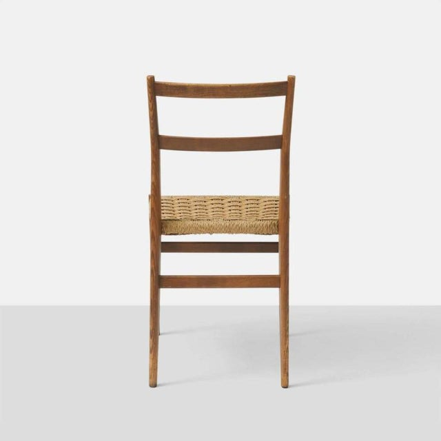 A set of eight dining chairs by Gio Ponti in ash with rush seats woven in a basket weave pattern, all retaining their...