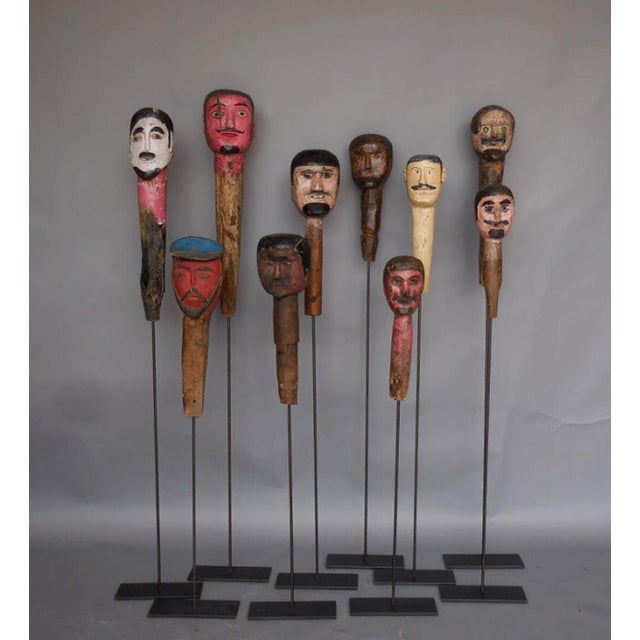 Collection of antique Gigantes (giant) heads from Guatemala. Carved wood heads held by indigenous people on stilts,...