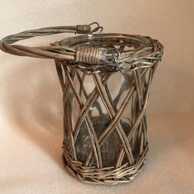 Woven wicker cachepot or candle holder with glass insert and woven handle.