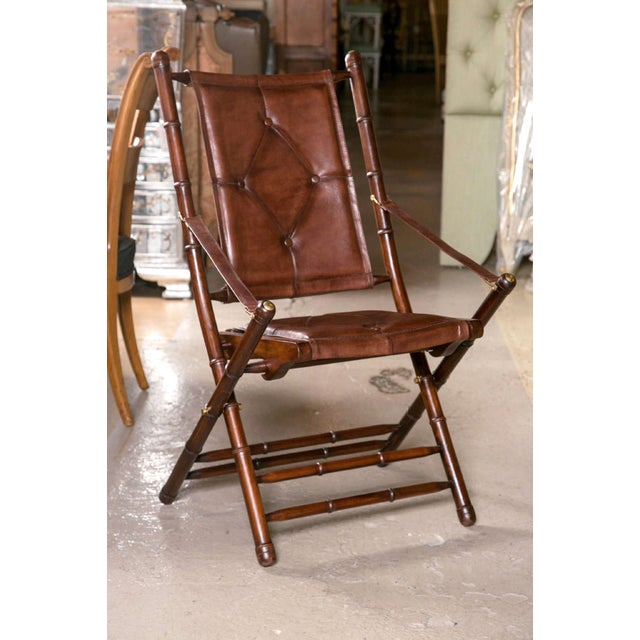 20 Bamboo form folding chairs. Each feature a fine button-tufted, slightly distressed leather seat and back rest. All...