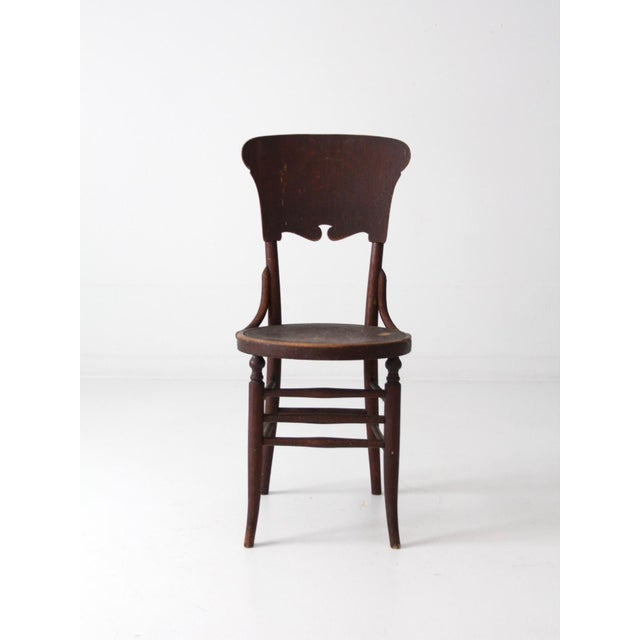 This is an antique round seat chair. The dark brown bentwood chair features turned legs and a decorative shield back...